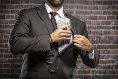 Uomo corrotto che tiene le fatture di soldi fotografie stock libere da diritti