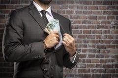 Uomo corrotto che tiene le fatture di soldi fotografia stock libera da diritti