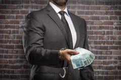 Uomo corrotto che tiene le fatture di soldi immagini stock