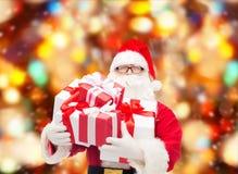Uomo in costume del Babbo Natale con i contenitori di regalo Fotografia Stock