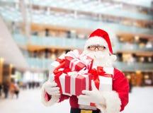 Uomo in costume del Babbo Natale con i contenitori di regalo Immagini Stock
