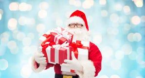 Uomo in costume del Babbo Natale con i contenitori di regalo Immagine Stock