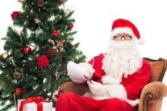 Uomo in costume del Babbo Natale con il blocco note Fotografie Stock Libere da Diritti