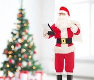 Uomo in costume del Babbo Natale con il blocco note e la borsa Fotografia Stock
