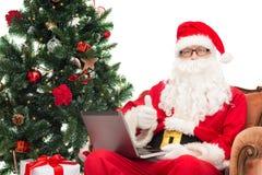 Uomo in costume del Babbo Natale con il computer portatile Fotografie Stock Libere da Diritti