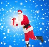 Uomo in costume del Babbo Natale con il contenitore di regalo Immagine Stock