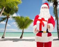 Uomo in costume del Babbo Natale con il contenitore di regalo Immagini Stock