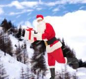 Uomo in costume del Babbo Natale con il contenitore di regalo Fotografia Stock