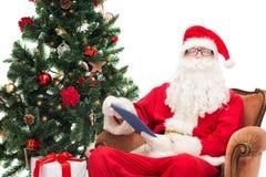Uomo in costume del Babbo Natale con il pc della compressa Immagini Stock