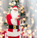 Uomo in costume del Babbo Natale con il pc della compressa Fotografia Stock