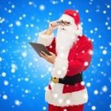 Uomo in costume del Babbo Natale con il pc della compressa Immagini Stock Libere da Diritti