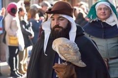 Uomo in costume medievale che tiene uccello predatore alla parata tradizionale del festival medievale di Befana di epifania a Fir Fotografia Stock Libera da Diritti