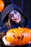 Uomo in costume spaventoso di Halloween con la zucca Immagini Stock