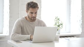 Uomo creativo che scrive sul computer portatile nell'ufficio del sottotetto video d archivio