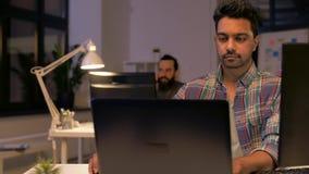 Uomo creativo con il computer portatile che funziona all'ufficio di notte stock footage