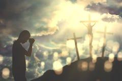 Uomo cristiano che prega a Dio con tre croci immagine stock