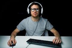 Uomo in cuffia avricolare che gioca il video gioco del computer Immagini Stock