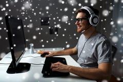 Uomo in cuffia avricolare che gioca il video gioco del computer a casa Fotografia Stock