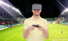 Uomo in cuffia avricolare di realtà virtuale sopra il campo di football americano Immagini Stock Libere da Diritti