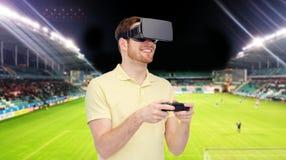 Uomo in cuffia avricolare di realtà virtuale sopra il campo di football americano Immagine Stock Libera da Diritti