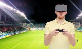 Uomo in cuffia avricolare di realtà virtuale sopra il campo di football americano Fotografie Stock