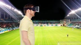 Uomo in cuffia avricolare di realtà virtuale sopra il campo di football americano Fotografie Stock Libere da Diritti