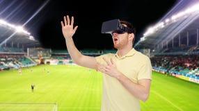 Uomo in cuffia avricolare di realtà virtuale sopra il campo di football americano Immagine Stock