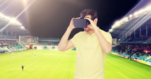 Uomo in cuffia avricolare di realtà virtuale sopra il campo di football americano Fotografia Stock