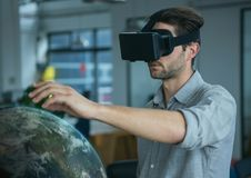 Uomo in cuffia avricolare di VR che tocca un pianeta 3D Fotografie Stock
