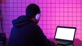 Uomo in cuffia che gioca video gioco a casa Visualizzazione bianca fotografia stock libera da diritti