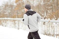 Uomo in cuffie che corre lungo il ponte di inverno Fotografie Stock