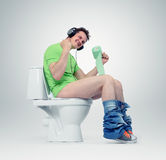 Uomo in cuffie che si siedono sulla toilette Sì! Fotografia Stock