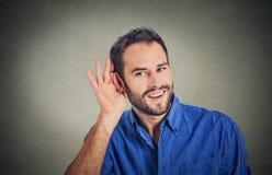 Uomo curioso bello di affari che ascolta segreto dentro sulla conversazione, mano all'orecchio Fotografia Stock