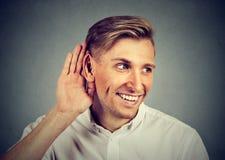 Uomo curioso che ascolta segreto dentro sulla mano di conversazione l'orecchio Fotografia Stock Libera da Diritti