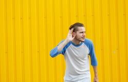 Uomo curioso che origlia e che ascolta qualcosa su un fondo giallo Concetto ascoltante di nascosto Copi lo spazio Fotografie Stock Libere da Diritti