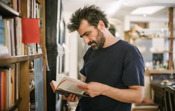 Uomo curioso che sceglie libro nella sua biblioteca a casa Immagini Stock