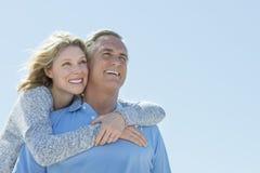 Uomo d'abbraccio della donna da dietro mentre distogliendo lo sguardo contro il cielo Fotografia Stock Libera da Diritti