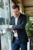 Uomo d'affari accanto alla finestra fotografia stock