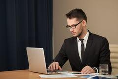 Uomo d'affari ad una battitura a macchina dell'area di lavoro Fotografia Stock Libera da Diritti