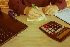 Uomo d'affari ad uno scrittorio in un ufficio che scrive su un computer portatile e su un calcolatore Fotografia Stock