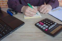 Uomo d'affari ad uno scrittorio in un ufficio che scrive su un computer portatile e su un calcolatore Fotografie Stock Libere da Diritti