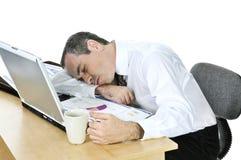Uomo d'affari addormentato al suo scrittorio su priorità bassa bianca immagini stock libere da diritti