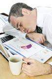 Uomo d'affari addormentato al suo scrittorio su priorità bassa bianca immagine stock