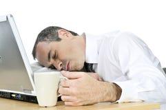 Uomo d'affari addormentato al suo scrittorio su priorità bassa bianca Fotografia Stock