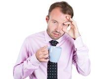Uomo d'affari addormentato molto stanco e quasi di caduta che tiene una tazza di caffè, lottando per non schiantarsi e non restare Fotografie Stock Libere da Diritti