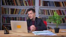 Uomo d'affari adulto attraente che ha una video chiamata sul computer portatile che si siede nell'ufficio con gli scaffali per li video d archivio