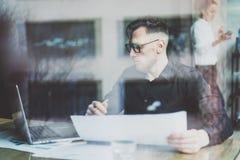 Uomo d'affari adulto barbuto che lavora al caffè urbano moderno Finestra della depressione della foto Uomo che porta camicia nera fotografia stock libera da diritti