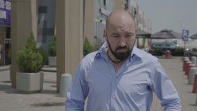 Uomo d'affari adulto che gode del ballo della via nel ritmo del latino di salsa contro la costruzione della città di affari - stock footage