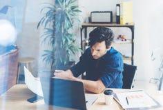 Uomo d'affari adulto che lavora al posto di lavoro soleggiato sul computer portatile mentre sedendosi alla tavola di legno SMan e fotografia stock