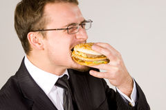 Uomo d'affari affamato che mangia hamburger immagine stock libera da diritti